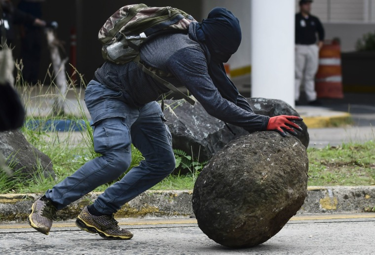 Image: A masked protester pushes a boulder during protests