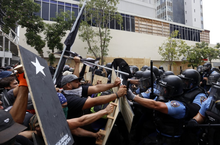Image: Protesters clash with police following a May Day march in San Juan