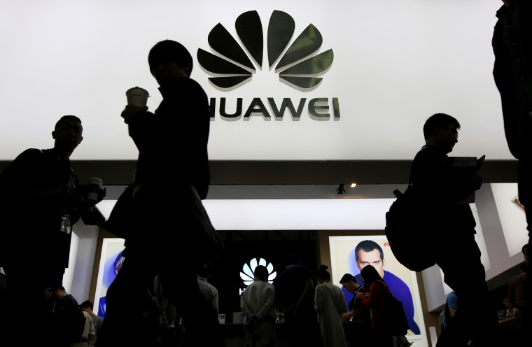 Image: People walk past a sign board of Huawei at CES Asia 2016 in Shanghai