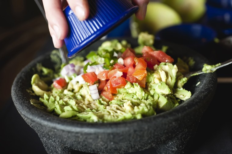 Image: A woman adds diced tomatoes and onions over a bowl of guacamole