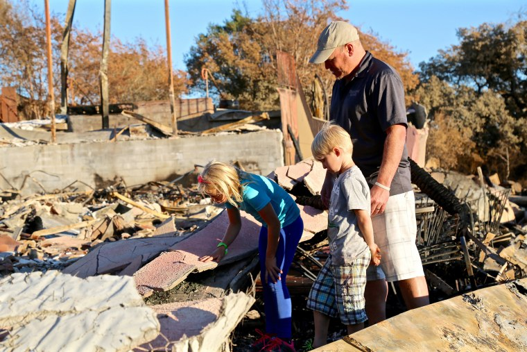 Image: Rene Byck brings son Brycen, age 6, and daughter Adianka, age 9, to the site where their family-owned Paradise Ridge Winery stood until it was reduced to rubble by the Tubbs Fire on Oct. 9, 2017.