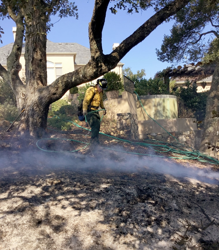 Image: WDS firefighters apply water in their effort to completely extinguish the fire near Giuffrida's home in October 2017.
