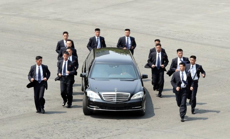 Image: Bodyguards escort a car carrying North Korean leader Kim Jong Un