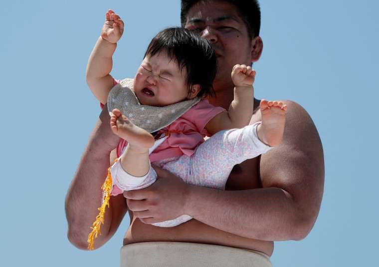 Image: A baby cries in the arms of an amateur sumo wrestler during a baby crying contest at Sensoji temple in Tokyo