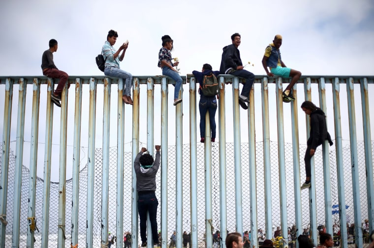 Image: Members of a caravan of migrants from Central America climb up the border fence between Mexico and the U.S., as a part of a demonstration prior to preparations for an asylum request in the U.S., in Tijuana