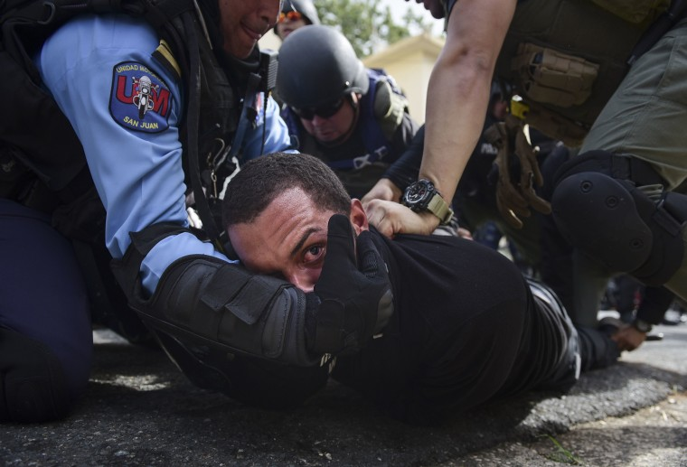 Image: Police detain a protester after a May Day march turned violent in San Juan