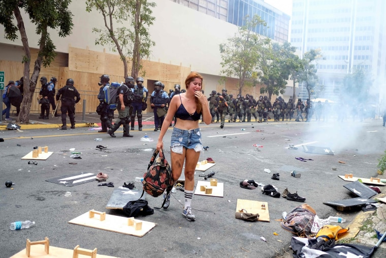 Image: A woman cries in front of a riot police line after tear gas was deployed during a May Day