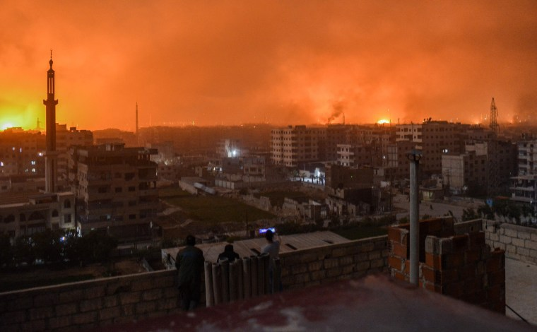 Image: People watch explosions over the skyline of the Syrian capital of Damascus