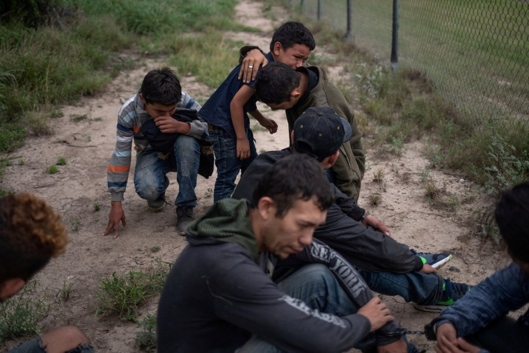Image: A four-year-old boy weeps in the arms of a family member as he and others were apprehended by border patrol agents