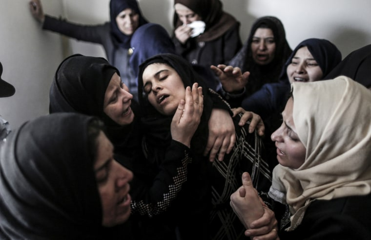 Image: Mourners console the mother of 15-year-old Palestinian teenager