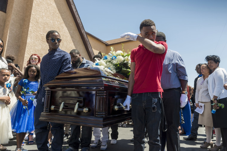 "Image: A pallbearer wipes a tear at the end of the funeral for Diante ""Butchie"" Yarber"