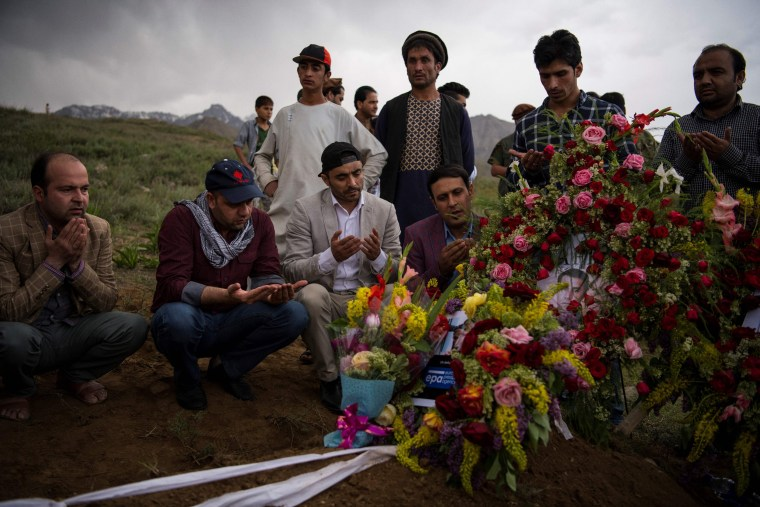 Image: Friends and relatives of Agence France Presse chief photographer Shah Marai Faizi gather at his burial