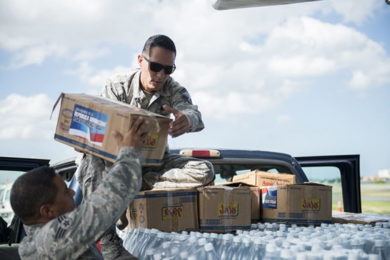 Senior Master Sgt. Jan Paravisini, a maintenance management analyst with the 156th Airlift Wing, loads supplies onto a truck, Nov. 22, 2017, in Isla Grande Airport, Puerto Rico.