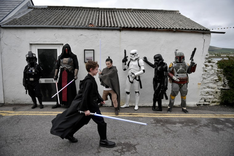 "Image: A young Star Wars fan walks past others in costume on ""May the Fourth be with you"" day"