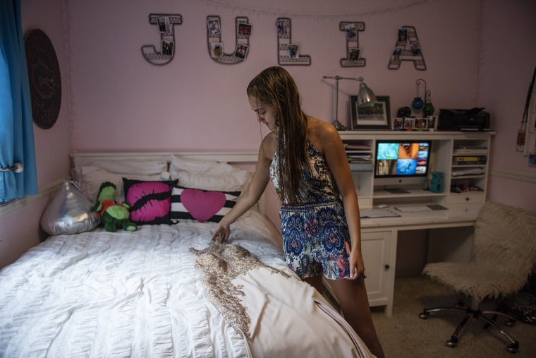 Image: Julia Cordover looks at her dress at her home