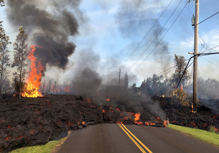 Image: Lava from a fissure slowly advances to the northeast on Hookapu Street after the eruption of Hawaii's Kilauea volcano