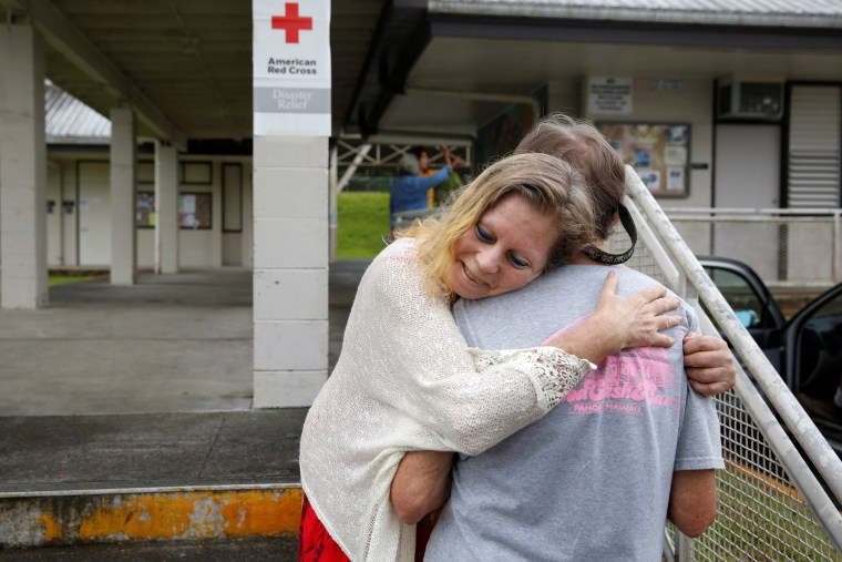 Image: Carolyn McNamara hugs her neighbor Paul Campbell at an evacuation center in Pahoa after moving out of their homes after the Kilauea Volcano erupted, in the Puna community in Hawaii