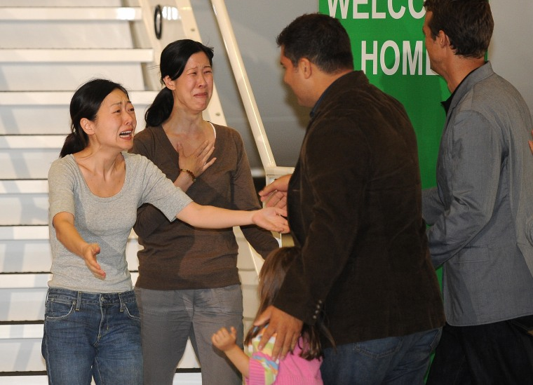 Euna Lee and Laura Ling embrace their family after being released from North Korea in 2009.