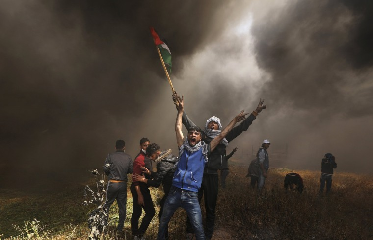 Image: Palestinian demonstrators shout during clashes with Israeli troops at a protest at the Israel-Gaza border east of Gaza City