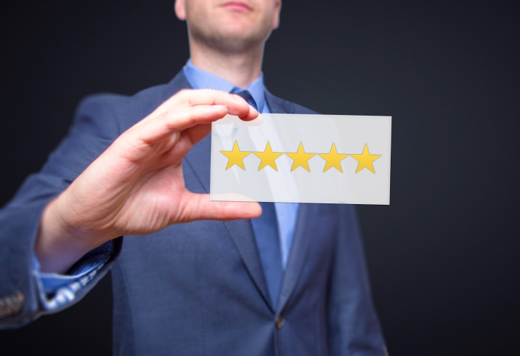 Businessman hand holding five stars isolated on black background. Business rating concept. Stock Photo