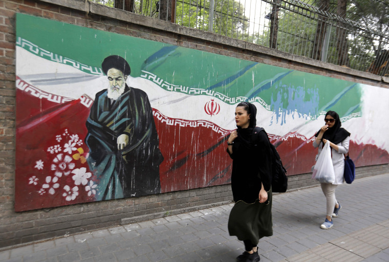 Image: An Iranian woman walks past a mural in Tehran