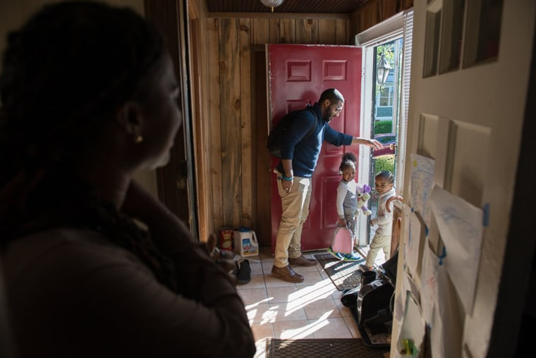 Image: Alia McCants looks on as her husband and children leave their home in White Plains, New York.