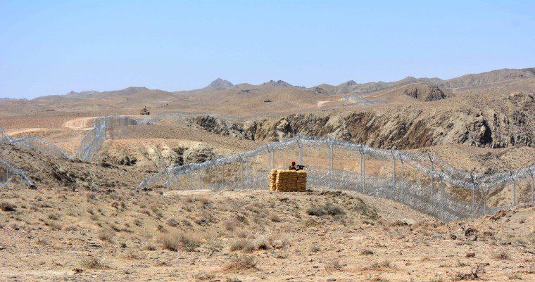 Image: A Pakistani army soldier stands guard along with border fence with Afghanistan