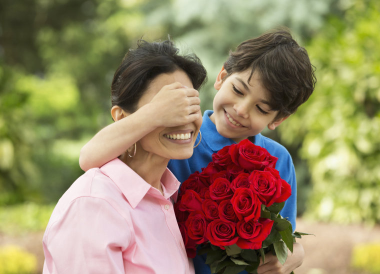 Image: Hispanic boy giving mother bouquet of roses
