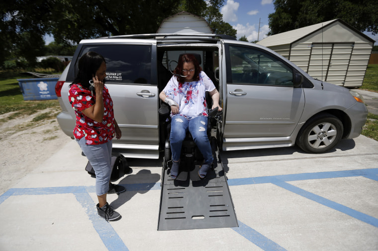 Image: Jamie Duplechine exits her van with help from direct service professional Deborah Broussard