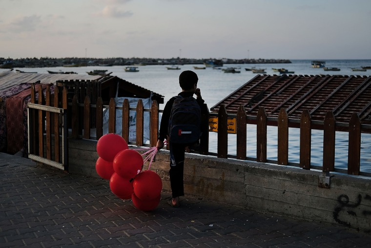 Image: A child looks out at the sea at a fishing port in Gaza City