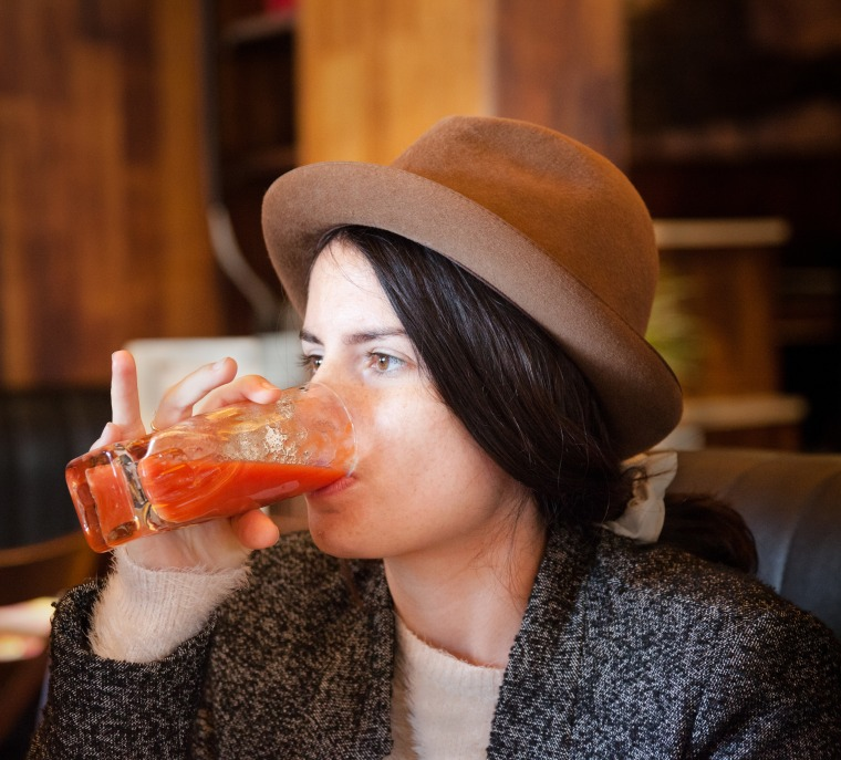 quirky girl with trilby hat enjoys tomato juice in cafe