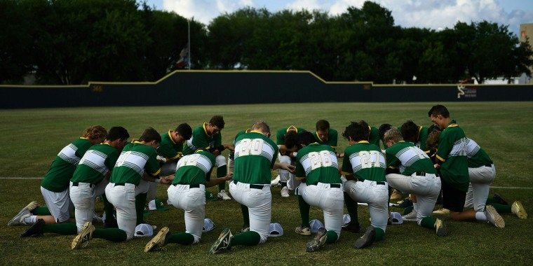 Players of the Santa Fe High School baseball team kneel together in a moment of prayer.