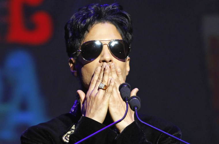 Image: Singer Prince gestures as he announces upcoming live dates at the Apollo Theater in New York