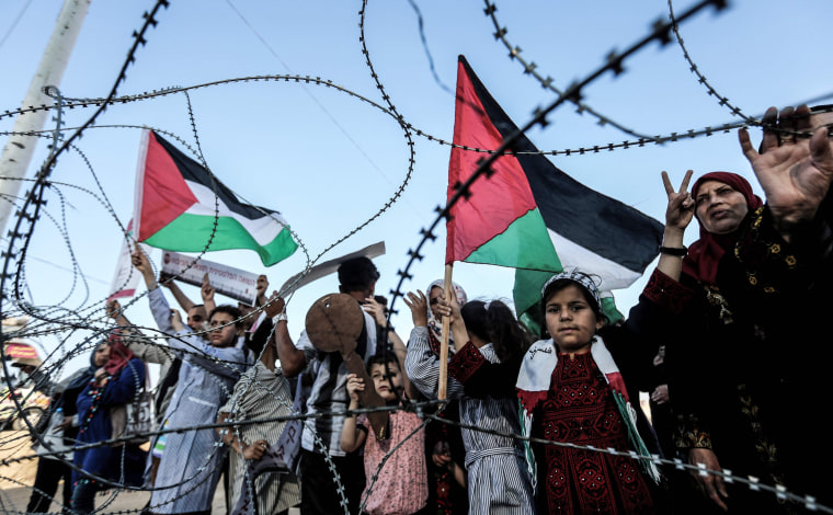 Image: Palestinians stand near fence between the Gaza Strip and Israel