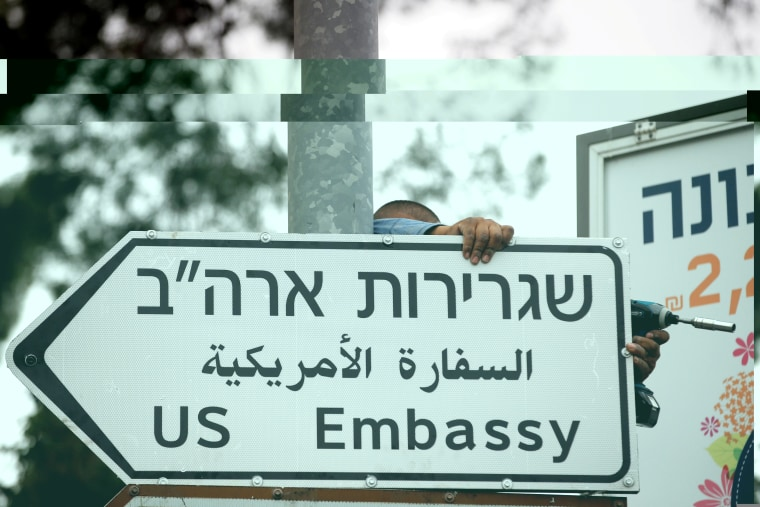 Image: A worker hangs a sign showing directions to the U.S. Embassy in Jerusalem