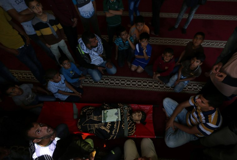 Image: People gather around the body of a Palestinian, who was killed during a protest at the Israel-Gaza border, during his funeral at a mosque in Khan Younis in the southern Gaza Strip