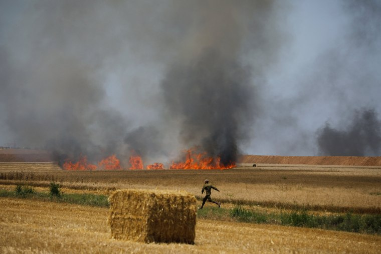 Image: An Israeli soldier runs in a field which has caught fire, close to the Israeli side of the border fence between Israel and Gaza near kibbutz Mefalsim