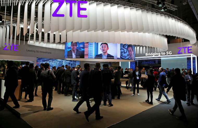 Image: FILE PHOTO: People stand at ZTE's booth during Mobile World Congress in Barcelona