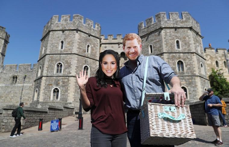 Image: A couple wear Prince Harry and Meghan Markle face masks outside Windsor Castle, in Windsor