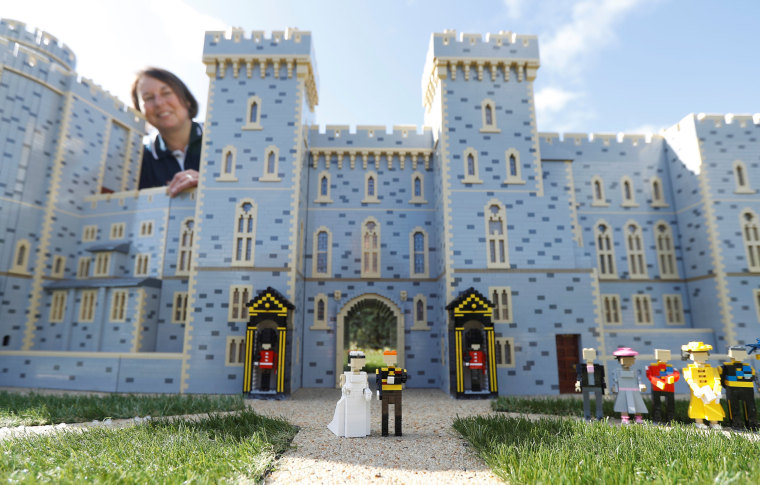 Image: Head model maker, Paula Laughton poses for a photograph with a LEGO Windsor Castle replete with royal wedding between Britain's Prince Harry and Meghan Markle, in Windsor