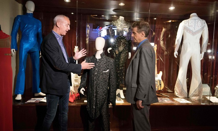 Image: Martin Nolan, executive director of Julien's Auctions, speaks with a reporter about Prince's Under the Cherry Moon ensemble