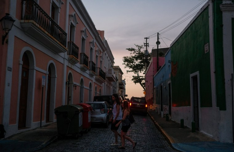 Image: Tourists walk through Old San Juan during a power outage