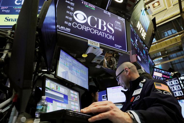 Image: A trader works below the CBS Corporation logo on the floor of the New York Stock Exchange