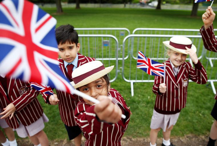 Image: School children in uniform wave Union Jack Flags