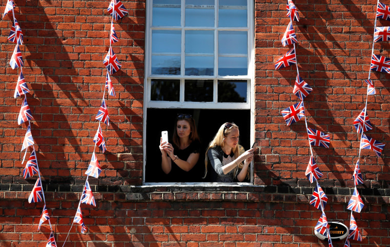 Image: Women take photos on their smartphones as they lean out of the window of a building near Windsor Castle in Windsor