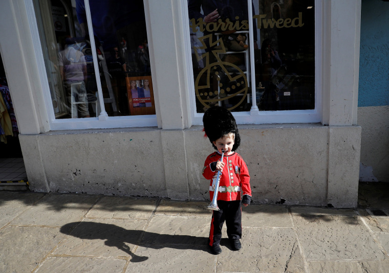 Image: Alex Tonkin, 2, wears a replica Guardsman's uniform as he plays with his trumpet ahead of Prince Harry and Meghan Markle's wedding, in Windsor