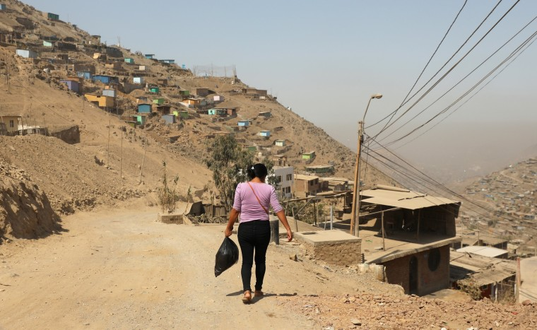 Image: A woman walks at a hill in the shanty town Nueva Esperanza on the outskirts of Lima