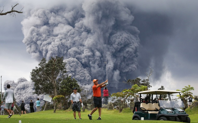Image: An ash plume from the Kilauea volcano rises in the distance behind golfers