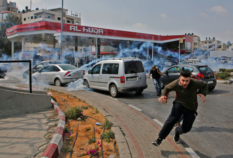 Image: Palestinians run away from tear gas shot at them by Israeli forces during a protest in Ramallah