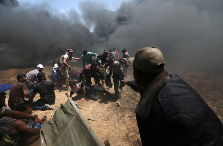 Image: A wounded Palestinian demonstrator is evacuated as others take cover from Israeli fire and tear gas